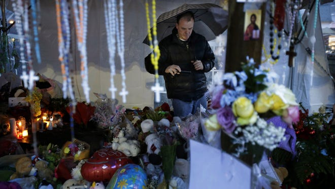 Ben Toby of Sandy Hook visits a memorial to the Newtown shooting victims during a heavy rain in Newtown, Conn.