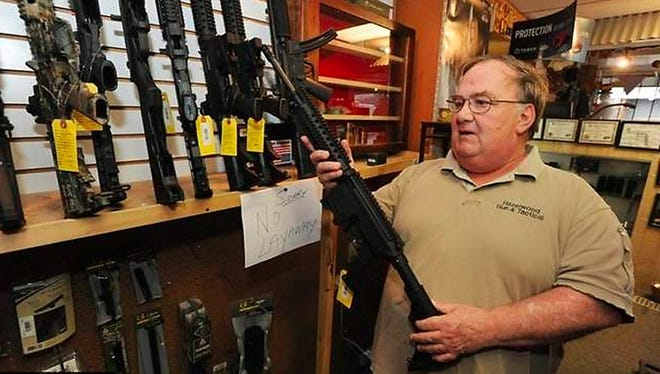 Cecil Brown, owner of Hazelwood Gun in Waynesville, N.C., said assault weapons such as these Smith and Wesson AR- 15s are flying off the shelf and the shop had sold out of top-of-the-line Colt rifles. Thirty-round AR-15 clips were selling briskly as well.