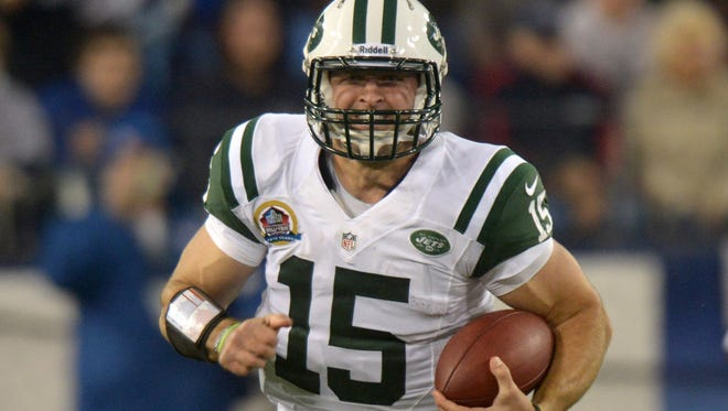 New York Jets quarterback Tim Tebow (15) carries the ball against the Tennessee Titans at LP Field.