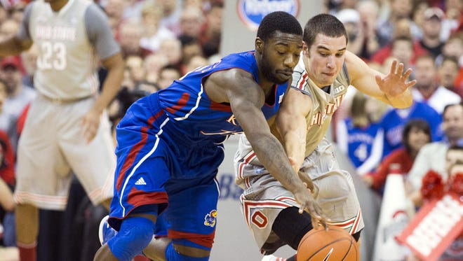 Ohio State Buckeyes guard Aaron Craft (4) tries to steal the ball from Kansas Jayhawks guard Elijah Johnson (15) at Value City Arena.