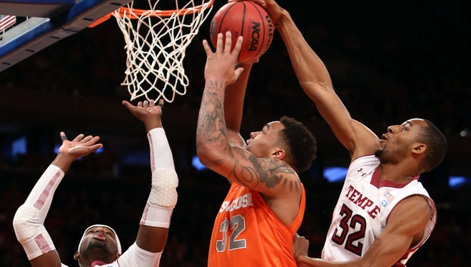 Syracuse Orange forward DaJuan Coleman (32) shoots between Temple Owls forward Rahlir Hollis-Jefferson (32) and forward Anthony Lee (3) during the first half at Madison Square Garden.