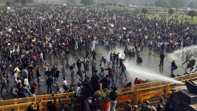 Indian protesters shout slogans as policemen use water cannons to disperse the crowds in New Delhi on Saturday.