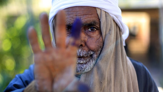 An Egyptian elderly man shows his inked finger after casting his vote on the second round of a referendum on a disputed constitution drafted by Islamist supporters of President Mohammed Morsi in Fayoum, Egypt, on Saturday.