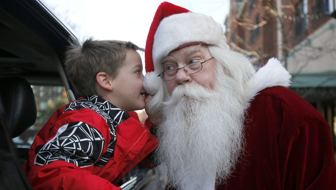 AJ Farner, 5, of Bloomfield Hills, Mich., whispers his Christmas list to Santa Mike Short, a professional Santa from Westland, Mich., while his family visits downtown Birmingham, Mich.
