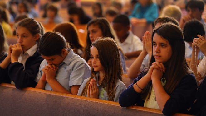 Grace Romanik, Jenny Rotondo and Victoria Gonzalez pray during a service at St. Rose of Lima for the victims of the Sandy Hook Elementary shooting in Newtown, Conn., on Friday.