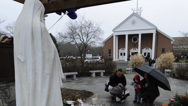 People gather at a memorial outside  St. Rose of Lima Roman Catholic Church on Sunday morning in Newtown, Conn.