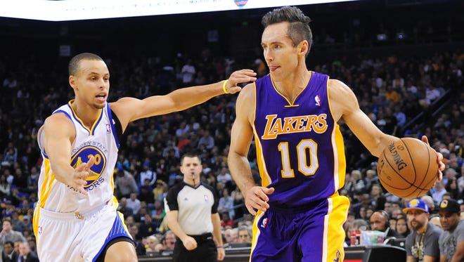 Los Angeles Lakers point guard Steve Nash (10) dribbles the ball against Golden State Warriors point guard Stephen Curry (30) during the first quarter at ORACLE Arena.