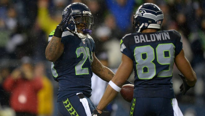 Seattle Seahawks running back Marshawn Lynch (24) celebrates with receiver Doug Baldwin (89) after scoring on a 9-yard touchdown reception in the first quarter against the San Francisco 49ers at CenturyLink Field.