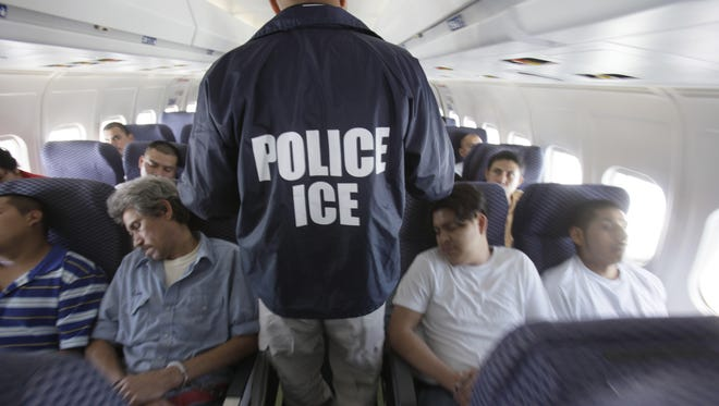 An Immigration and Customs Enforcement agent walks among immigrants being deported in 2010.
