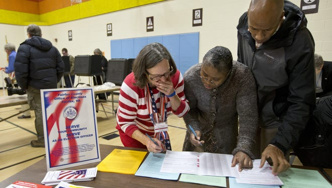 Assistant Election Officer Belinda Strickland, center, assists voters on Nov. 6, in Fairfax County, Va.