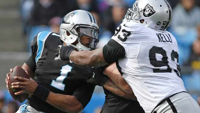 Raiders defensive lineman Tommy Kelly grabs Panthers quarterback Cam Newton during Sunday's game.