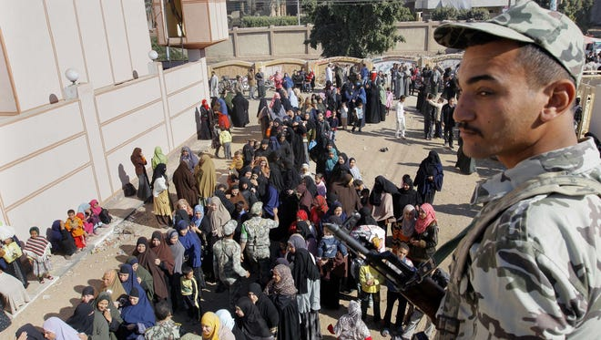 An Egyptian soldier stands guard in front of hundreds of women waiting to vote on the constitution.