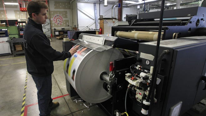 Digital press operator Steve Foster at Mercury Printing in Rochester, N.Y., feels for wrinkles in the paper on the company's Kodak Prosper 5000XL injet press. Kodak is pinning its hopes for recovery from bankruptcy on digital printing.