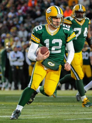 Aaron Rodgers scrambles for a six-yard touchdown in the first quarter.