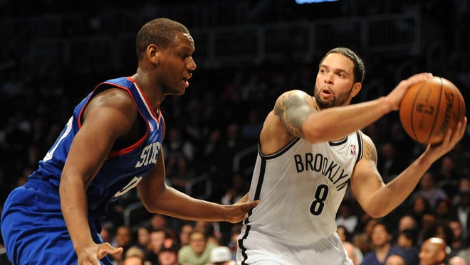Nets guard Deron Williams (8) attempts to make a pass around 76ers center Lavoy Allen during Brooklyn's 95-92 win.