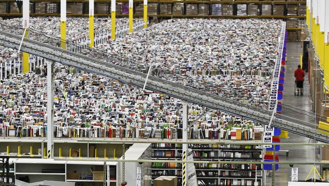 An employee walks a wide isle at Amazon.com's 1.2 million square foot fulfillment center in Phoenix on Cyber Monday.