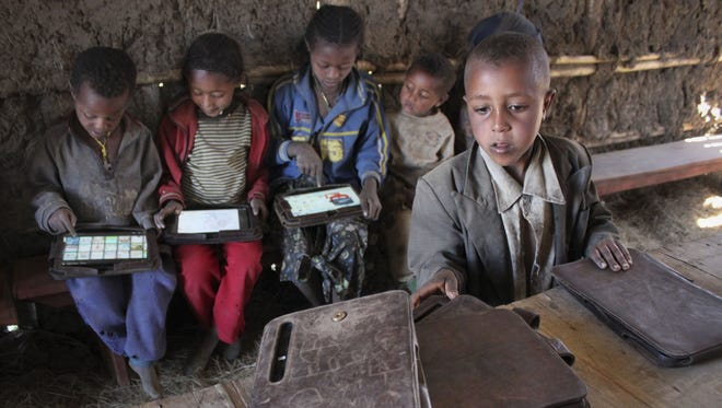 A boy looks for his tablet computer as others play with theirs which were given by the One Laptop Per Child project in the village of Wenchi, Ethiopia.