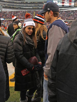 Mila Kunis and Ashton Kutcher watched from the sidelines as the Chicago Bears took on the Green Bay Packers in Chicago Dec. 16.