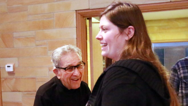 Monsignor Anthony Majchrowski, 93, spends time talking with Janelle Lusty, 19, after 7 a.m. mass at All Saints Catholic Church in Flint. Mich. Lusty and her family stayed to decorate the church for the holidays. Standing in back is Paul Tomaszewski, 51.
