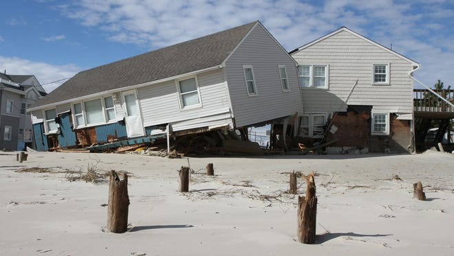 A house that washed off its pilings during superstorm Sandy crashed into another house in the Brant Beach section of Long Beach Township, N.J. New sand dunes had not built in this section of the township because of disputes over government access to private properties.