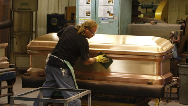 Troy Hawkins puts finishing touches on a bronze casket at Hillenbrand Inc.'s  Batesville Casket Company in Batesville, Ind., Thursday Nov. 29, 2012.