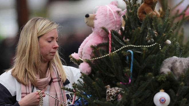 Kat Donohue of Newtown helps to decorate donated Christmas trees placed in front of the  Sandy Hook School on Dec. 16.