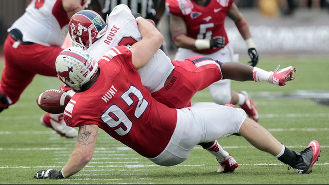 Southern Methodist defensive end Margus Hunt (92) tackles Fresno State running back Robbie Rouse, causing a fumble during the second quarter.