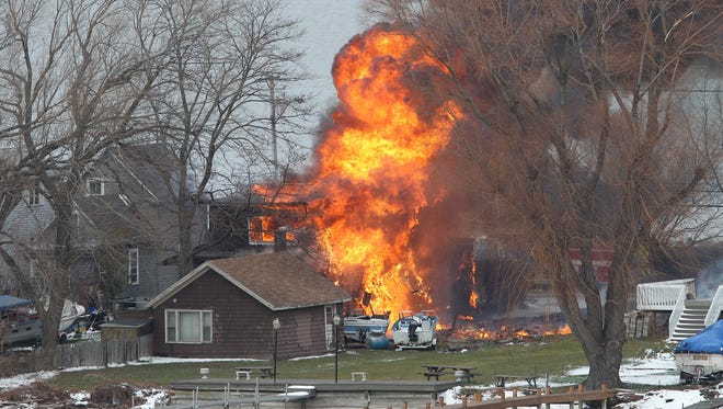 A house  burns  after a man set fire  and then shot and killed a responding police officer and a firefighter while injuring two other firefighters.  The man was later found dead. Monday December 24, 2012 in Webster, New York.  (Via OlyDrop)