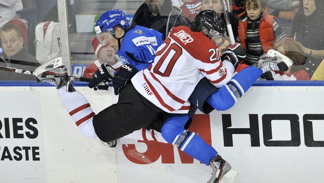 Canada forward Boone Jenner, front,  takes out Team Finland forward Markus Granlund during last year's tournament.