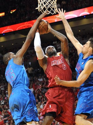 Heat forward LeBron James splits Thunder defenders Kevin Durant, left, and Nick Collison during Tuesday's 103-97 win.