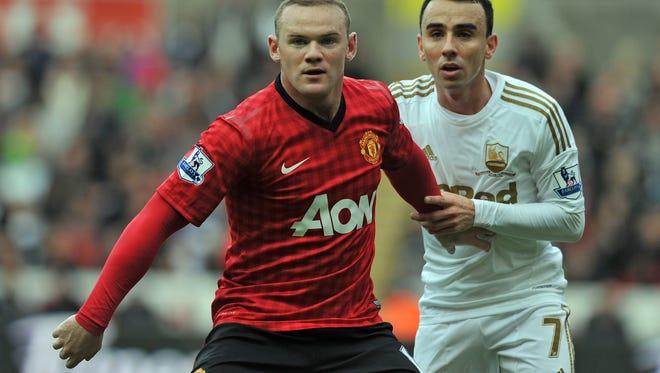 Manchester United's English striker Wayne Rooney, left, and Swansea City's English midfielder Leon Britton battle Dec. 23.