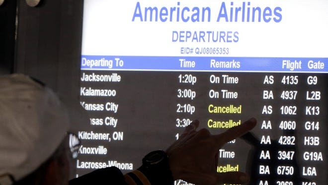 A passenger checks a American Airlines flight information screen at O'Hare airport in Chicago on Dec. 20, 2012. Storms continued to cause cancellations on Dec. 26 as travelers returned home from their holiday breaks.