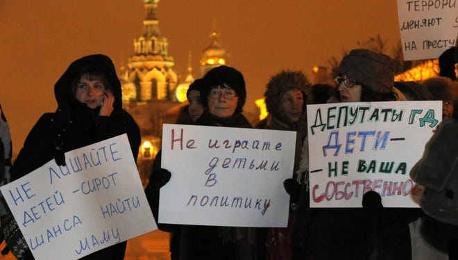 """Opposition activists hold posters reading """"Do not involve children in politics"""" and """"Lawmakers, children are not your  ownership"""" during a protest against a bill banning U.S. adoptions of Russian children in St. Petersburg, Russia, on, Dec. 26."""