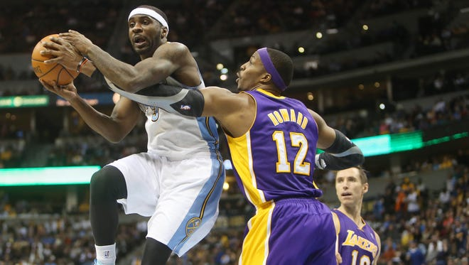 Denver Nuggets guard Ty Lawson drives to the basket while being defended by Los Angeles Lakers center Dwight Howard.