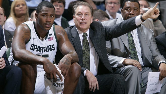 Michigan State coach Tom Izzo, center, sits next to Derrick Nix, left, on the bench during the second half of a game against Texas in East Lansing, Mich. At right is associate head coach Dwayne Stephens. Michigan State won 67-56.