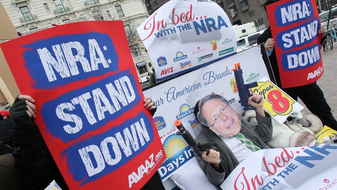 Members of the activist group Avaaz protest today's NRA press conference.