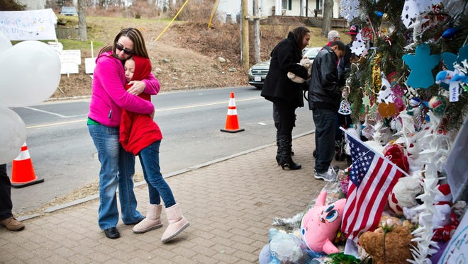 Deborah Gibelli holds her daughter, Alexandra Gibelli, while looking at a memorial for those killed in the school shooting at Sandy Hook Elementary School.