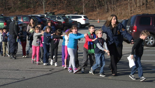 A Connecticut State Police officer leads children out of Sandy Hook Elementary School in Newtown, Conn., on Dec. 14.