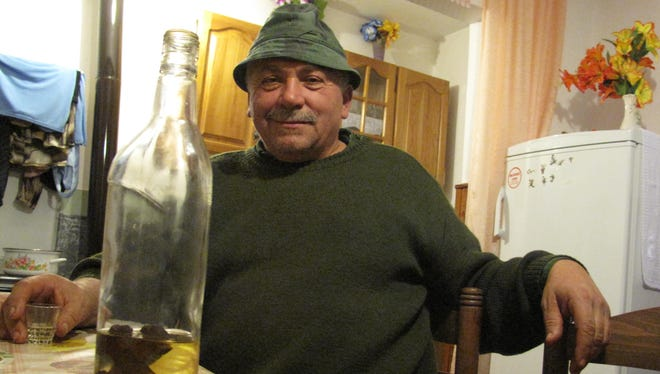 Holding a shot of homemade plum brandy with a wooden cross at the bottom of the bottle, 54-year-old farmer Milomir Aleksic insists the vampire Sava Savanovic is a regular visitor to his village.