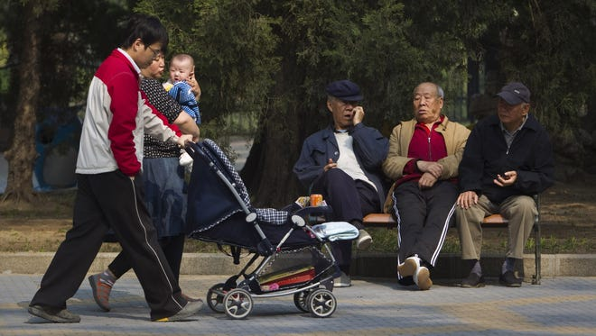 """Elderly men rest on a bench as a family with their newborn baby walks by at a park in Beijing in April. The Chinese legislature has amended its law on the elderly to require that adult children visit their aging parents """"often"""" - or risk being sued by them."""