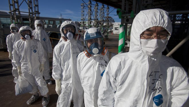 Workers in protective suits and masks wait to enter the emergency operation center at the crippled Fukushima Dai-ichi nuclear power station in Okuma, Japan, in 2011.