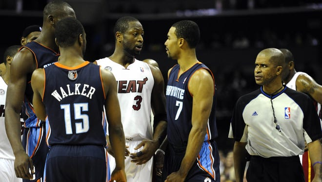 Heat guard Dwyane Wade, center, and Bobcats guard Ramon Sessions, right, disagreed on the intent of a groin kick Wade delivered Wednesday.
