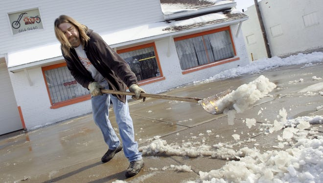 Paul Glasscock, part-owner of The Cycle Shop, in Marion, Ind., clears snow and slush from in front of the business on Thursday.