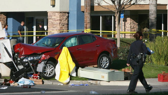 A car rests against a damaged sign on Magnolia Ave., where a motorist jumped the curb and struck four people at a bus stop.