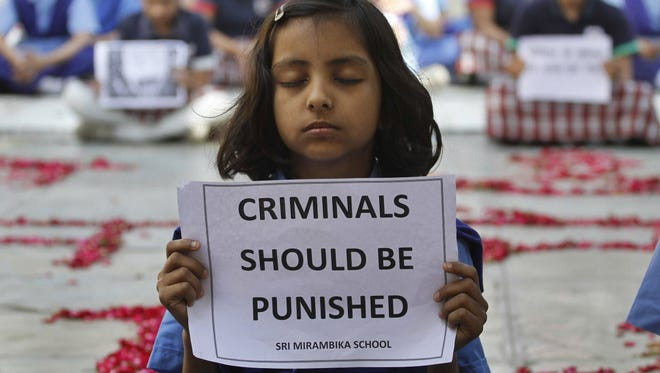 An Indian schoolgirl holds a placard during a prayer ceremony to mourn the death of a 23-year-old gang rape victim, at a school in Ahmadabad, India, on Saturday.