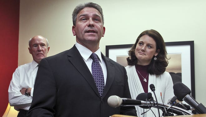 Minnesota State-Mankato football coach Todd Hoffner speaks to reporters as his wife, Melodee, and attorney Gerald Maschka listen.