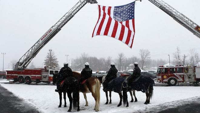 Mounted police and fire trucks stand by the entrance during the calling hours for Lt. Mike Chiapperini and Tomasz Kaczowka at Webster Schroeder High School Saturday afternoon, December 29, 2012. Kris J. Murante, Rochester (N.Y.) Democrat and Chronicle