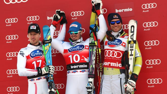 From left, Dominik Paris of Italy and  Hannes Reichelt (C) of Austria stand on the podium  with Aksel Lund Svindal (right) of Norway after the  men's downhill on Saturday in Bormio, Italy. Paris and Reichelt tied for first.