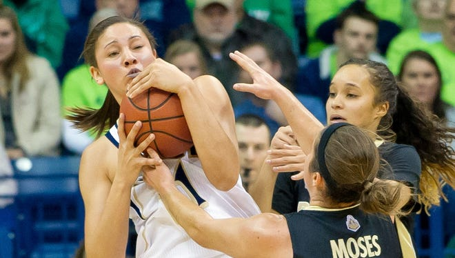 Notre Dame's Natalie Achonwa keeps the ball way from Purdue's Courtney Moses, front, and KK Houser.