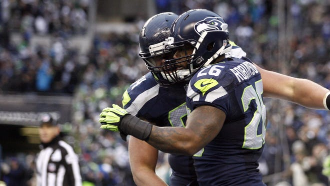 Seattle Seahawks fullback Michael Robinson (26) celebrates a touchdown reception against the St. Louis Rams with guard J.R. Sweezy (64) during the third quarter.